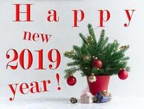 Em um fundo claro há uma árvore de Natal decorada com luzes em um potenciômetro vermelho sob ele Presentes dos cones foto de stock