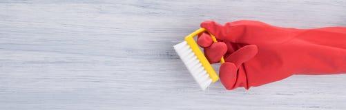 em um fundo claro, uma mão em uma luva vermelha, guarda uma escova para limpar, há um lugar para uma inscrição foto de stock royalty free