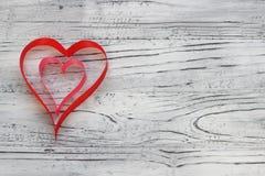 Em um fundo de madeira branco das fitas fez dois corações valenti Fotografia de Stock