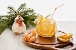 Em um fundo de madeira com bebida no copo de vidro claro com fatias de laranjas e de limões com a figura de uma galinha do pássar fotografia de stock