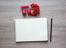 Em um fundo de madeira encontra-se uma folha vazia de um caderno em um lápis da mola e em cubos de um calendário de mesa de Rowan imagem de stock