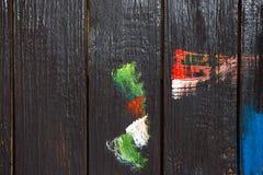 Em um fundo de madeira, que seja pintado com a pintura preta pintada com cores diferentes de manchas da pintura fotografia de stock royalty free