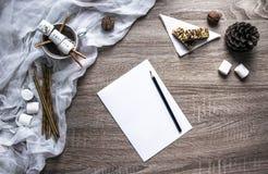 Em um fundo de madeira uma folha branca e um lápis preto e à esquerda uma disposição dos marshmallows e do doce foto de stock