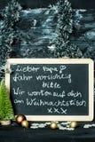 Em um fundo do Natal um quadro-negro com uma mensagem da criança a genar: Conduza com cuidado, nós estão esperando-o foto de stock