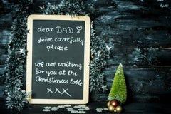 Em um fundo do Natal um quadro-negro com uma mensagem da criança a genar: Conduza com cuidado, nós estão esperando-o imagens de stock royalty free