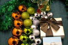 Em um fundo reflexivo preto, uma cesta de vime com bolas do Natal As mentiras da cesta em seu lado e no desenrolamento das bolas  Fotografia de Stock