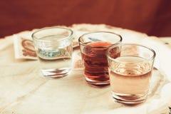 Em um fundo vermelho de pano há três vidros com álcool e dinheiro velho da União Soviética do período soviético, a vida de Imagem de Stock