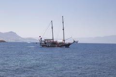 Em um mar calmo, um iate bonito navega com os turistas na parte traseira Imagens de Stock