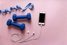 Em um smartphone azul do telefone do centímetro da fita da cor dos pesos do fundo do rosa com os fones de ouvido brancos Imagens de Stock