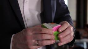 Em uma cara do ` s de Rubik o cubo é escrito o ` resolve o ` As mãos do homem de negócios no escritório que resolve o cubo do ` s vídeos de arquivo