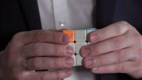 Em uma cara do ` s de Rubik o cubo é escrito o ` resolve o ` O homem de negócios entrega a resolução do enigma do cubo do ` s de  vídeos de arquivo