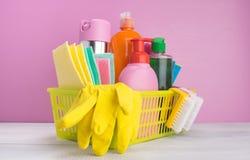 Em uma cesta amarela, em um fundo cor-de-rosa, um grupo de artigos para limpar, panos, esponjas, escovas, líquidos para a desinfe imagens de stock royalty free