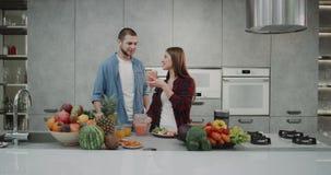 Em uma cozinha moderna com um par bonito do projeto na manhã usando um misturador que faz um batido saudável junto video estoque