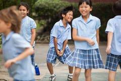 Em uma faculdade em Banguecoque, as crianças têm o divertimento no dur do campo de jogos Foto de Stock