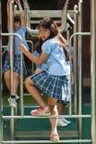 Em uma faculdade em Banguecoque, as crianças têm o divertimento no dur do campo de jogos Fotos de Stock