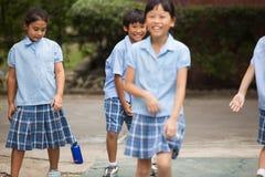 Em uma faculdade em Banguecoque, as crianças têm o divertimento no dur do campo de jogos Foto de Stock Royalty Free