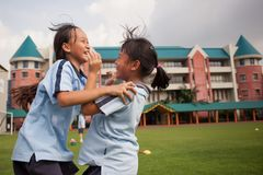Em uma faculdade em Banguecoque, as crianças têm o divertimento no dur do campo de jogos Imagens de Stock