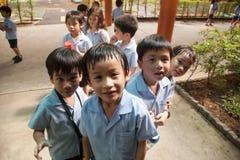 Em uma faculdade em Banguecoque, as crianças têm o divertimento no dur do campo de jogos Fotografia de Stock