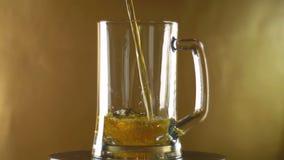 Em uma grande caneca que transforme em uma cerveja escura derramada em um fundo dourado, Oktoberfest fotos de stock royalty free