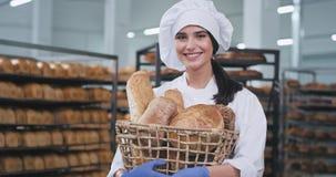 Em uma indústria de padaria grande na frente da senhora atrativa da câmera com o sorriso bonito que mantém uma cesta com fresco c filme