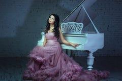 Em uma menina da sala escura que senta-se no piano Fotos de Stock Royalty Free