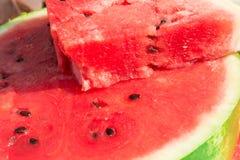 Em uma metade uma melancia encontra-se uma parte triangular de melancia Imagens de Stock Royalty Free
