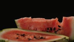 Em uma metade uma melancia encontra-se uma parte triangular de melancia, fundo preto do close-up Fotos de Stock Royalty Free