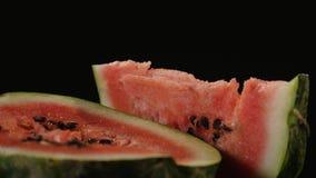 Em uma metade uma melancia encontra-se uma parte triangular de melancia, fundo preto do close-up Fotografia de Stock