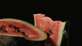 Em uma metade uma melancia encontra-se uma parte triangular de melancia, fundo preto do close-up Fotografia de Stock Royalty Free