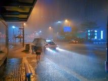 Em uma noite chuvosa, saia o trabalho na parada do ônibus e espere o ônibus foto de stock royalty free