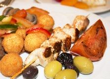 Em uma placa há um shashlik da galinha com batatas, azeitonas, ol fotografia de stock royalty free