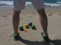 Em uma praia ensolarada de Califórnia, um jogador do bocce está na frente das bolas, planeando seu próximo passo imagens de stock