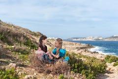 Em uma rocha no litoral em um ninho enorme com ovos sente duas meninas vestidas nas mãos feericamente da posse dos pássaros e olh Imagem de Stock Royalty Free