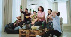 Em uma sala de visitas espaçoso uma empresa grande dos amigos apreciam o tempo ao olhar um fósforo de futebol na frente do vídeos de arquivo