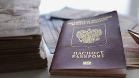 Em uma tabela branca h? muito dinheiro, um passaporte e um avi?o pequeno feitos do dinheiro O conceito do resto imagem de stock