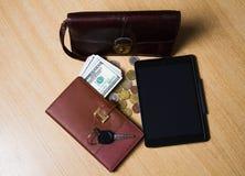 em uma tabela de madeira coloque o dinheiro, o caderno, a tabuleta, o saco acessível e as chaves ao carro Imagens de Stock