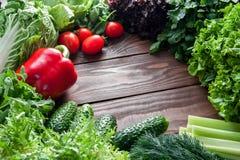 Em uma tabela de madeira são os vegetais, a salada e os verdes verdes e vermelhos com um lugar para inscrição no centro fotografia de stock
