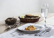 Em uma tabela um guardanapo com uma placa do guisado vegetal um o vidro da forquilha e um ramo de um ninho do ` s do salgueiro co fotos de stock