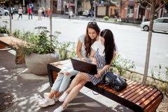 Em uma tarde ensolarada, duas senhoras bonitas novas com cabelo escuro longo imagens de stock