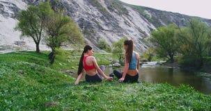 Em uma vista colocada verde surpreendente com as pedras grandes duas senhoras que apreciam o tempo junto depois que um exercício  vídeos de arquivo