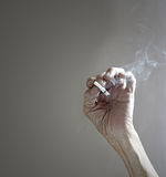 Emaciated hand holding cigarette Royalty Free Stock Image