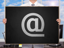 Email. Businessman holding blackboard with drawing email symbol Royalty Free Stock Images