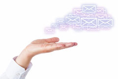 Email Cloud Leaving The Palm Of A Hand On White. Numerous email icons rising from an open palm of a hand to shape a virtual cloud. Business symbol or metaphor stock images