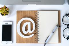 Email comcept. Contact us for feedback. Desktop with notepad, smartphone, glasses and email symbol. Top view stock photo