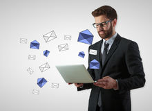 Email communication concept. Businessman using laptop with e-mail letters on gray background. Email communication concept royalty free stock photo