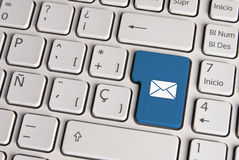 Email concept, mail envelope keyboard key. Spanish keyboard with email concept mail envelope icon over blue background button. Image with clipping path for easy Royalty Free Stock Image