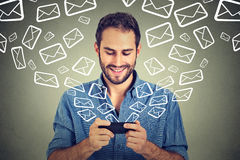 Email d'invio occupati dei messaggi del giovane uomo felice del ritratto dallo Smart Phone Fotografia Stock Libera da Diritti