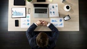 Email de la lectura del hombre de negocios en el ordenador portátil en la oficina, vista superior de la tabla foto de archivo