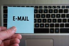 EMAIL di parola sulla tenuta appiccicosa della nota a disposizione sul fondo della tastiera immagine stock
