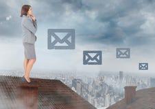 Email ikony i bizneswoman pozycja na dachu z miastem kominowym i chmurnym Fotografia Stock
